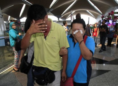 A man and woman wipe tears from their eyes after walking out of the reception centre at at Kuala Lumpur International Airport.