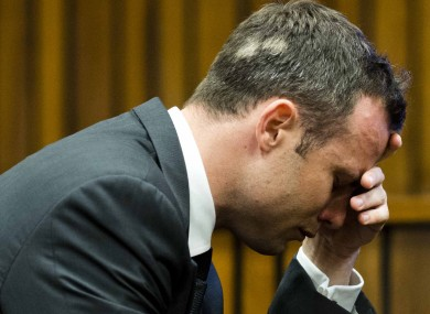 Oscar Pistorius puts his hand to his face while listening to cross questioning about the events surrounding the shooting death of his girlfriend Reeva Steenkamp