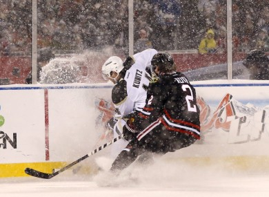 Chicago Blackhawks' Duncan Keith (2) and Pittsburgh Penguins left wing Chris Kunitz (14) kick up snow and ice as they battle for a loose puck.