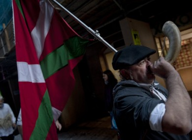 A man dressed in traditional local clothes carries a Basque flag and plays a horn as he takes part in a pro-independence Basque march calling for release of all Basque prisoners of the Basque armed group ETA.