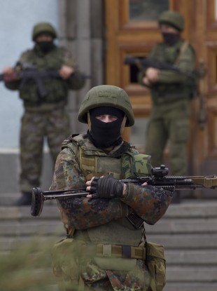 Unidentified armed men guard the entrance to the local government building in downtown Simferopol, Ukraine today.