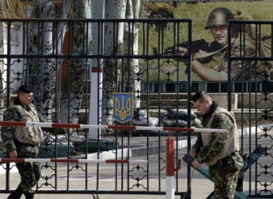 Ukrainian soldiers stand guard at the gate of a military base in the port of Kerch in Crimea.