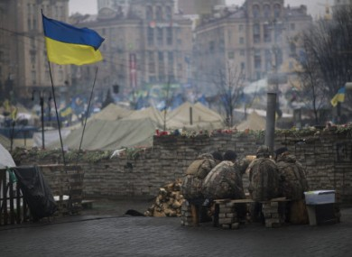 Anti-Yanukovych protesters warm themselves next to a fire in Kiev's Independence Square, Ukraine