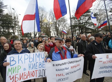 Pro-Russia demonstrators hold Russian and Crimean flags and posters.