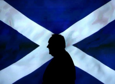 Scottish First Minister Alex Salmond walking in front of a Saltire.