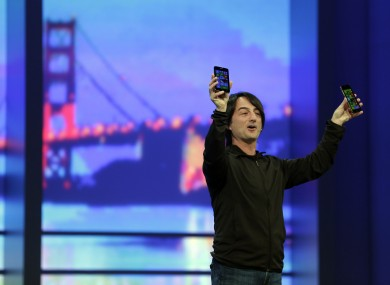 Microsoft corporate vice president Joe Belfiore, holds up new phones using the new Windows 8.1 during the keynote address of the Build Conference.