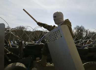 A masked man stands atop of a barricade at the regional administration building in in Donetsk.