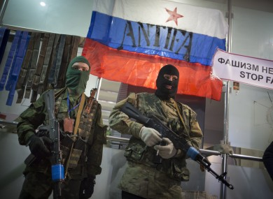 Masked pro-Russian gunmen guard an entrance of the Ukrainian regional office of the Security Service with a Russian National flag is in background in Luhansk, Ukraine.