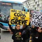 Demonstrators hold up signs that read in Portuguese