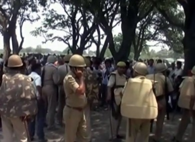 Police stand amongst the crowd near where two teenage sisters were found hanging from a mango tree in the Katra village.