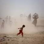 Pakistanis run as they get caught in a sand storm on the outskirts of Islamabad, Pakistan. The temperature in the capital city reached 40 degrees Celsius. <span class=