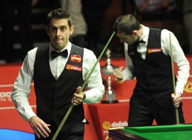 Ronnie O'Sullivan leaves the arena as Mark Selby celebrates winning the final frame of the afternoon session.