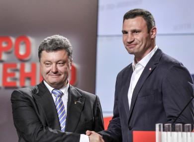 Ukrainian presidential candidate Petro Poroshenko, left, shake hands with Vitali Klitschko.