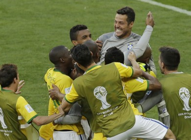 Brazil's goalkeeper Julio Cesar is mobbed by team-mates after they win the penalty shootout.