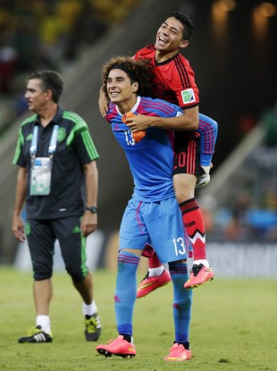 Ochoa gives Mexico teammates Javier Aquino a piggyback after the 0-0 draw with Brazil.