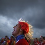 A soccer fan wearing a Mohawk-styled wig in Chile's team colors, cheers as he watches a live broadcast of the group B World Cup match between Chile and Spain.<span class=