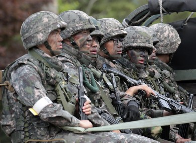 South Korean soldiers on a truck searching for the soldier who was on the run after the shooting