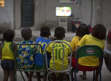 Children watch the World Cup opening match between Brazil and Croatia in an alley at the Mangueira slum, in Rio.