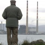 Man looking out on the, still standing, ESB Poolbeg Power Station.  Photographed by: Gareth Chaney <span class=