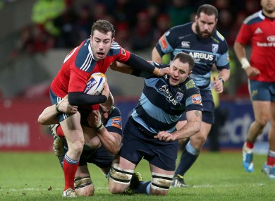 Munster's JJ Hanrahan with Macauley Cook and Chris Dicomidis of Cardiff.