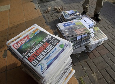 A man stands next to newspapers carrying headline stories and pictures of Thursday's Malaysia Airlines plane shot down, in Shah Alam, outside Kuala Lumpur, Malaysia
