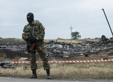 A pro-Russian fighter guards the crash site