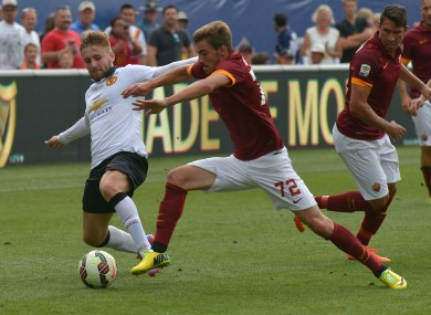Luke Shaw of Manchester United and Mikai Balasa of Roma battle for the ball.