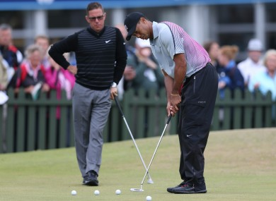 Woods practices putting with Foley watching on (file photo).