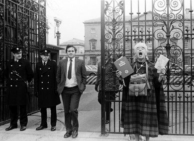Bertie Ahern, then Chief Whip of Fianna Fáil outside Leinster House, as former school teacher Margaret dances in honour of the Holy Trinity and Virgin Mary.