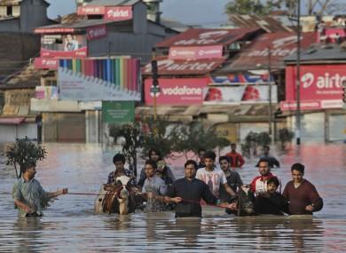 Kashmiri men move with their cattle from their flooded neighborhood in Srinagar.