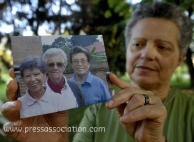 Silvia Marsili shows a photo of the three Italian missionary nuns, from left, Bernardetta Boggian, Olga Raschietti and Lucia Pulici