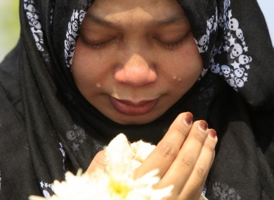 A Muslim woman cries as she waits outside Bunga Raya Complex at Kuala Lumpur International Airport before victims' bodies of the ill-fated Malaysia Airlines Flight MH17 are flown back