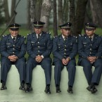 Soldiers are left to sit on a wall as they wait for the start of a military review in preparation for Independence Day celebrations in Mexico. <span class=
