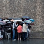 Visitors protect themselves from the rain with umbrellas prior to visiting La Sante prison, in Paris. <span class=