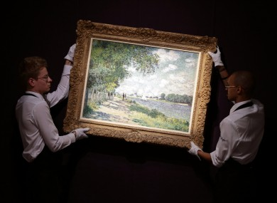 FILE: Gallery staff holding a different work by Claude Monet, La Seine a Argenteuil, 1875
