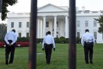 Secret Service officers walk along the lawn at the White House following the incident