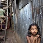 A Bangladeshi child stands in an alley as a boy climbs a ladder outside their home at a slum in Dhaka, Bangladesh. (AP Photo/A.M. Ahad)<span class=