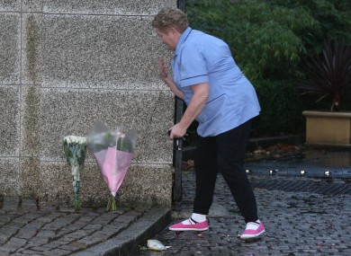A local leaves flowers at the scene at Ballybrack yesterday.