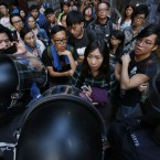 Upset pro-democracy students are moved as riot police clear their encampment in the Mong Kok district of Hong Kong. Riot police moved in on the Mong Kok pro-democracy protest zone in a dawn raid on Friday, taking down barricades, tents and canopies that have blocked key streets for more than two weeks. (AP Photo/Wally Santana)<span class=