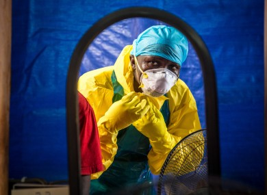 A health worker putting on protective clothing in Freetown, Sierra Leone last year