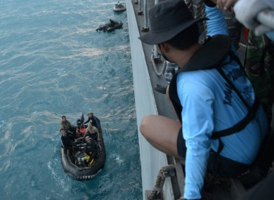 Indonesian navy divers prepare operations to lift the tail of the plane.