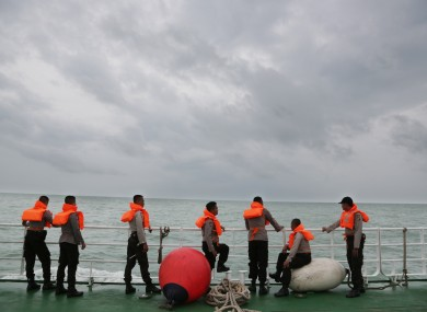 Indonesian police stand on the deck of a National Search And Rescue Agency ship earlier this month.