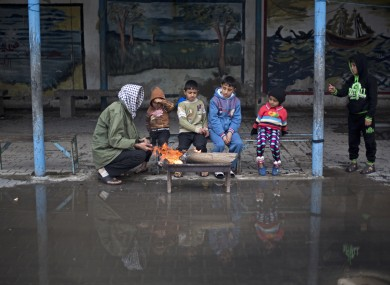 A Palestinian man sits with his children around fire to keep warm during a cold storm at a U.N. school where families live after their homes were destroyed by Israeli strikes in the summer, in Gaza City.