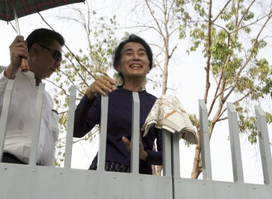 Aung San Suu Kyi smiles over the gates of her residence where she was under house arrest.