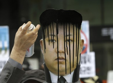 A South Koran protester spray paints a picture of Kim Jong Un