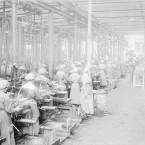 Interior of the National Shell Factory at Parkgate Street, Dublin, during the First World War. Note the board showing the number of shells passed into bond totals per shift on the back wall.