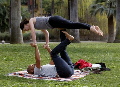 Neil Blan and Katherine Shea enjoy the outdoors as they practice yoga at Echo Park, Los Angeles.