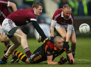 Kieran Donaghy releases the ball under pressure from Slaughtneil defenders.