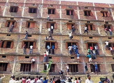 Indians climb the wall of a building to help students cheat in India.
