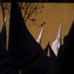 Hooded penitents from the La Paz brotherhood walk to the church to take part in a procession in Seville, Spain. Hundreds of processions take place throughout Spain during the Easter Holy Week. (AP Photo/Emilio Morenatti)<span class=